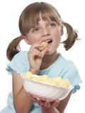 Liten flicka som äter en potatis, chips arkivbild