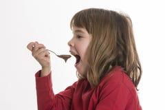 Liten flicka som äter en vaniljsås royaltyfri fotografi