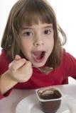 Liten flicka som äter en vaniljsås royaltyfri bild