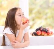 Liten flicka som äter ett äpple Arkivfoton