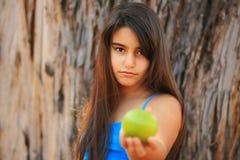 Liten flicka som äter ett grönt äpple Fotografering för Bildbyråer
