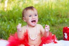 Liten flicka som äter hennes första kaka och le för födelsedag Royaltyfri Foto