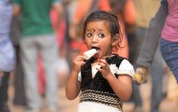 Liten flicka som äter ivrigt en glass royaltyfri bild