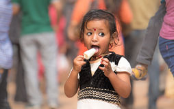 Liten flicka som äter ivrigt en glass royaltyfria foton