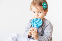 Liten flicka som äter klubban Lyckliga barn med ett stort läckert Arkivfoto