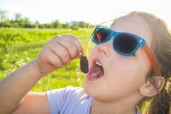 Liten flicka som äter mullbärsträdet med ingen wash Royaltyfri Fotografi