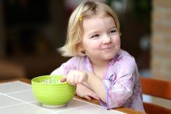 Liten flicka som äter mysli med yoghurten för frukost Arkivfoto
