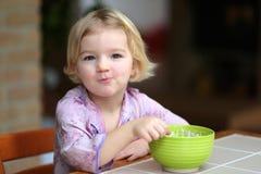 Liten flicka som äter mysli med yoghurten för frukost Arkivbild