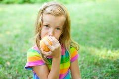 Liten flicka som äter persikan Royaltyfria Foton