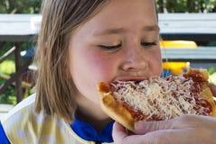 Liten flicka som äter pizza Royaltyfria Foton