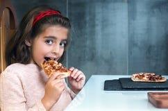 Liten flicka som äter pizza i en restaurang royaltyfria foton