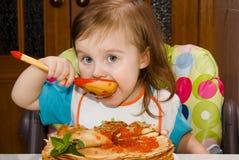Liten flicka som äter den röda kaviaren arkivfoto