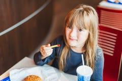 Liten flicka som äter snabbmat i ett kafé Arkivfoton