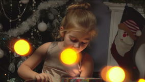 Liten flicka som öppnar en gåva arkivfilmer