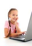 Liten flicka som använder datoren Arkivbilder