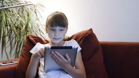 Liten flicka som använder den digitala minnestavlan arkivfilmer