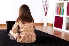 Liten flicka som använder en bärbar datordator Fotografering för Bildbyråer