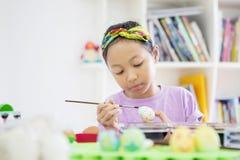 Liten flicka som använder en borste för att måla påskägg royaltyfria foton