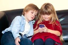 Liten flicka som använder en mobil som hålls ögonen på av hennes broder arkivbilder