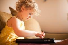 Liten flicka som använder minnestavladatoren Arkivfoto