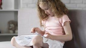 Liten flicka som använder minnestavlan för att spela lekar, modern utveckling, grejböjelse arkivfoto