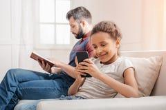Liten flicka som använder smartphonen medan faderläsebok på soffan Fotografering för Bildbyråer