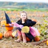 Liten flicka som bär den halloween häxadräkten på pumpalapp royaltyfri foto