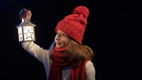 Liten flicka som bär den stack den vinterhatten och halsduken som går med lyktan arkivfilmer