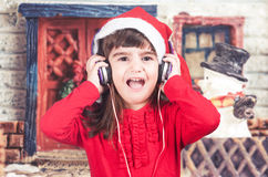Liten flicka som bär en jultomtenhatt som lyssnar till musik royaltyfria bilder