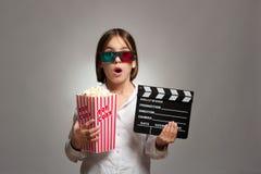Liten flicka som bär exponeringsglas 3D och äter popcorn Arkivbild