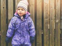 Liten flicka som bär purpurfärgat overallanseende vid trästaketet arkivbilder