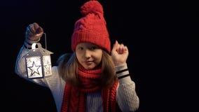 Liten flicka som bär stucken vinterhatt- och halsdukbelysning med lyktan arkivfilmer