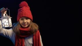 Liten flicka som bär stucken vinterhatt- och halsdukbelysning med lyktan stock video