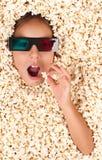 Liten flicka som begravas i popcorn Arkivfoto