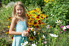 Liten flicka som bevattnar blommor royaltyfria foton