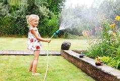 Liten flicka som bevattnar blommor i trädgården Arkivfoton