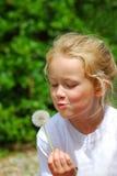 Liten flicka som blåser blowballen - maskros arkivbild