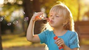 Liten flicka som blåser såpbubblor arkivfilmer