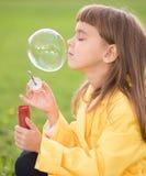 Liten flicka som blåser såpbubblor Arkivbilder