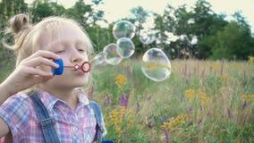 Liten flicka som blåser såpbubblor på en grön gräsmatta stock video