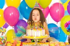Liten flicka som blåser stearinljus på födelsedagkakan royaltyfria bilder