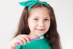 Liten flicka som borstar hans tänder med en tandborstetandläkekonsttand arkivfoto