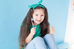 Liten flicka som borstar hans tänder med en tandborstetandläkekonsttand royaltyfri bild