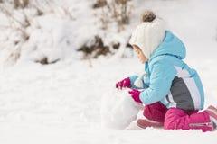 Liten flicka som bygger en snögubbe Royaltyfri Foto