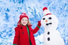 Liten flicka som bygger en snöman royaltyfri fotografi
