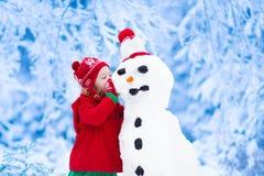 Liten flicka som bygger en snöman royaltyfria foton