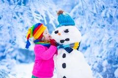 Liten flicka som bygger en snöman i vinter Arkivfoton