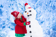 Liten flicka som bygger en snöman i vinter Arkivbild