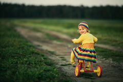 Liten flicka som cyklar på vägen Royaltyfri Foto