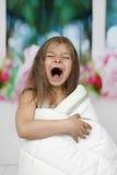 Liten flicka som dämpas i filtgäspningar Arkivfoto